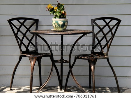 1c2c57943f3c9 Black wrought iron table and chairs on stone floor with clay vase of  flowers as centerpiece