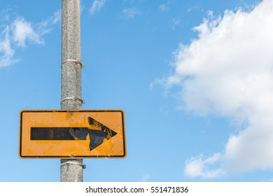 Black and yellow arrow sign on textured concrete pole pointing to the right. Blue sky and fluffy clouds background.