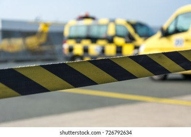 Black and yellow barrier tape at the airport with cars in the background