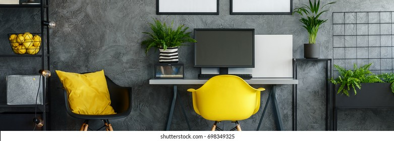 Black and yellow chair next to desk with desktop in dark room