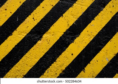 Black and yellow diagonal lines on a concrete background