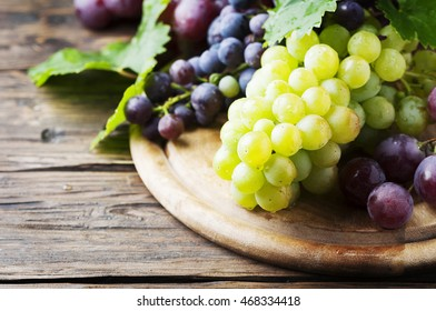 Black and yellow grape on the wooden table, selective focus