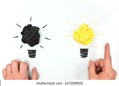 Black and yellow light bulb in white background flat lay with hands. Creativity, innovation and new business ideas concept.