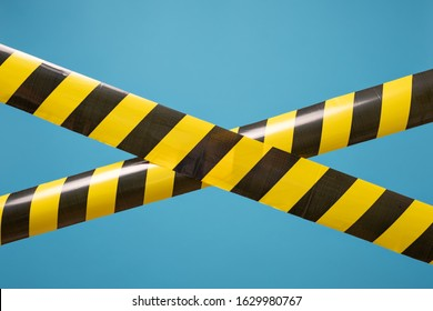 Black and yellow lines of barrier tape forbids passage. Concept of No entry. Protection from coronavirus.