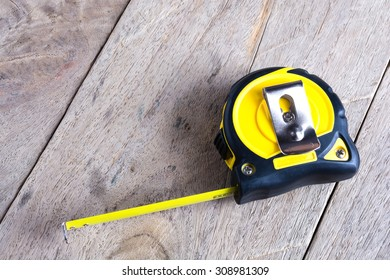 Black yellow Measuring Tape on wood background.
