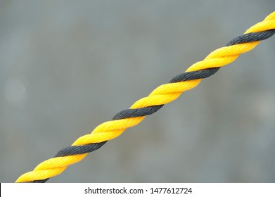 Black and yellow nylon rope. Nylon rope in diagonal direction. Isolated on blurred background. Close-up. Copy space.