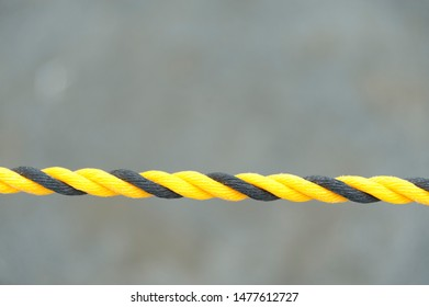 Black and yellow nylon rope. Nylon rope in horizontal direction. Isolated on blurred background. Close-up. Copy space.