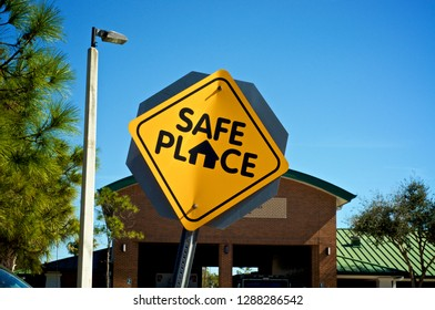 """A black and yellow """"safe place"""" street sign at entrance to fire station in Bonita Springs Florida"""