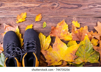 Black and yellow trekking boots on the floor with wooden boards and colorful autumn leaves