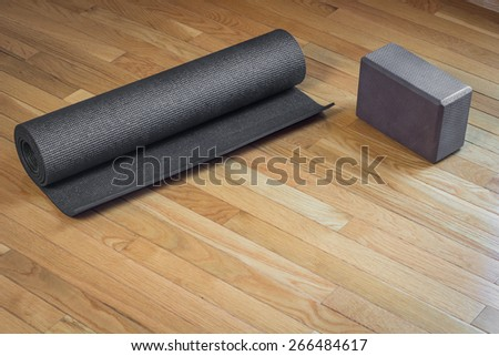 A black yoga mat rolled up next to a brown yoga mat on a wooden floor