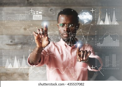 Black young businessman wearing glasses and casual shirt, holding hands like touching futuristic digital tablet with his fingers, making calculations, analyzing diagrams and schemes. Selective focus