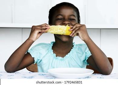 Black young girl eating corn cobb