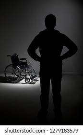 black young man silhouette, standing up is looking to a wheelchair, on dark gray background