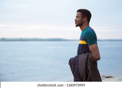 A black young man stands on the background of the river, the sea on his hand weighs his jacket, coat. Looking forward. into the future. Exchange student, fashionable look. Copy of space. Generation z.