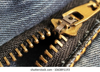 black zipper and lock on jeans background, so close