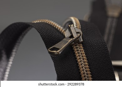 a black zipper opened to a gray surface