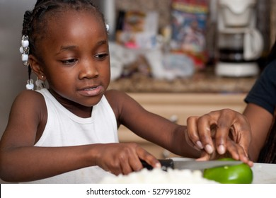 Black/African American girl cutting a green pepper.