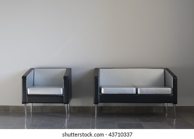 Black-and-silver modern chair and couch on a gray wall