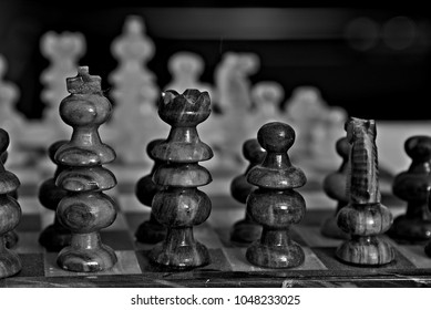 Black-and-white, closeup photograph of chess pieces. Blurry white pieces can be seen in the background.