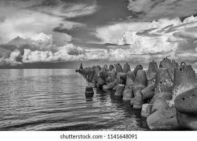 Black-and-white contrast photography with beautiful breakwaters and with incredibly beautiful colors and expressive clouds in the background. Perfect for advertising holidays on the sea