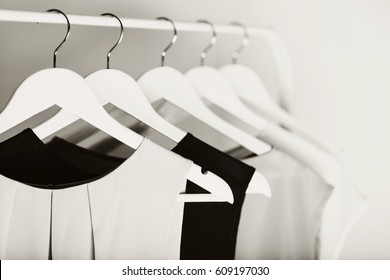 Black-and-white photo with the blur. Women's clothing on a white hanger. Selective focus.