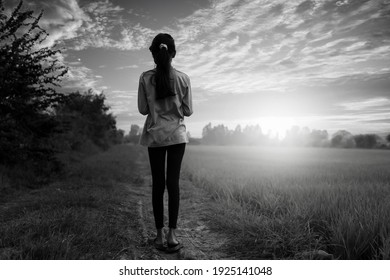 A black-and-white photo, a little girl standing alone and watching the sunrise in the morning in the field
