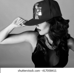 black-and-white photograph of a beautiful sexy young woman with attractive face wearing a baseball cap in the dance pose
