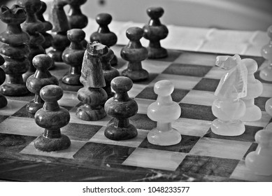 Black-and-white photograph of dusty chess pieces on a chess board.