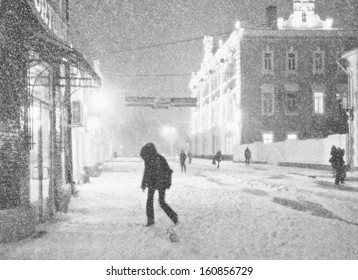 Black-and-white picture of the city street during a snow-storm. Some pedestrians hurry to take cover from a wind.
