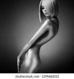 black-and-white portrait of beautiful nude woman with sexy body. Studio photography of young naked lady on grey background. Pretty blonde with perfect figure. Professional hair-dress and makeup.