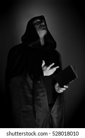 black-and-white portrait of a brutal man in a black robe with a book in their hands