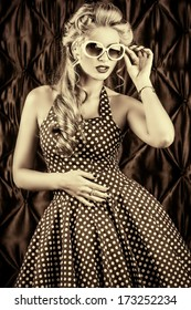 Black-and-white portrait of a charming pin-up woman with retro hairstyle and make-up.