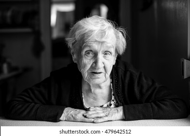 Black-and-white portrait of an elderly woman, close-up.