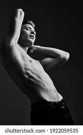 Black-and-white portrait of a handsome athletic young man with perfect muscular body. Sports and bodybuilding. Men's beauty and health.