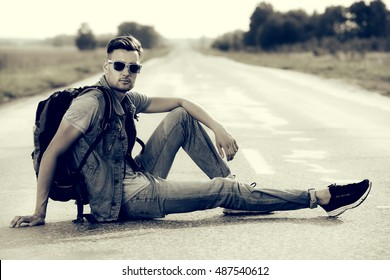 Black-and-white portrait of a handsome young man hitchhiker sitting on a highway. Adventure and tourism concept. Jeans style.