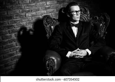 Black-and-white portrait of an imposing well dressed man sitting in a classic luxurious armchair. Luxury. Men's beauty, fashion.