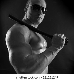 black-and-white portrait of a naked torso male bodybuilder athlete with a baton in a studio on a black background