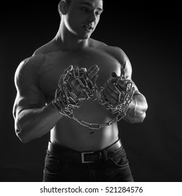 black-and-white portrait of a naked torso male bodybuilder athlete with the chain in the studio on a black background