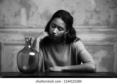 Black-and-white shot of attractive young African-American female in light clothes sitting relaxed at wooden table with shiny glass vase and touching hair