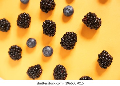 Blackberries and blueberries on an illuminating yellow background. High quality photo