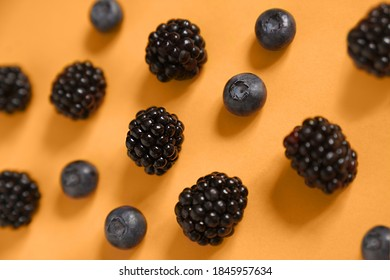 Blackberries and blueberries on a marigold background. High quality photo