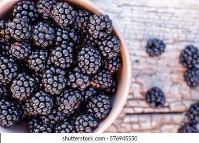 blackberries in a ceramic bowl on burlap cloth over wooden background close up. Rustic style, Selective focus