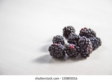 Blackberries on the white wood background