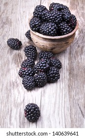 blackberries on wooden table with water drops background
