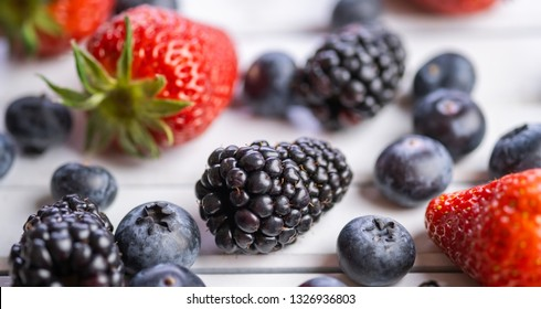 Blackberries with other berries on wooden white board. Selective focus.