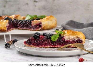 Blackberries pie with a slice on plate. Pie in summer with fresh picked wild blackberries