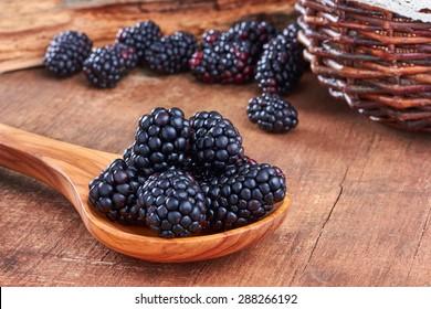 Blackberries in a spoon on wooden background