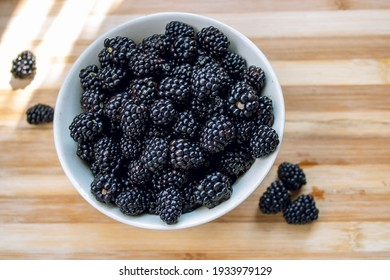 Blackberries in a white bowl on a wooden table