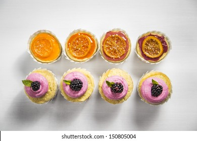Blackberry Buttercream and Candied Clementine Glazed Cupcakes in White Cupcake Wrappers on a White Wood Natural Background