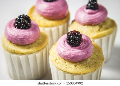 Blackberry Buttercream Vanilla Cupcakes in White Cupcake Wrappers on a White Wood Natural Background